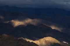 Tramonto nelle montagne: alte colline della cresta scura al crepuscolo e soltanto diversi picchi, illuminati dal sole e dal giall Immagini Stock