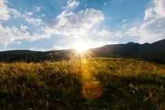 Tramonto nelle montagne su un prato alpino fotografie stock libere da diritti