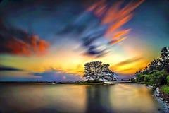 Tramonto nuvoloso e una spiaggia rocciosa con un'esposizione lunga Fotografie Stock