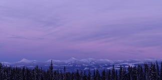 Tramonto porpora e blu sopra le montagne Fotografia Stock
