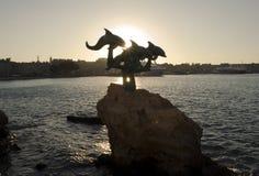 Tramonto, porto di Rodi, la statua dei delfini Immagini Stock Libere da Diritti