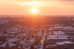 Tramonto rosso contro il contesto delle case nell'inverno, fumo leggero del villaggio dai tubi Vista superiore con sfuocatura Fotografia Stock