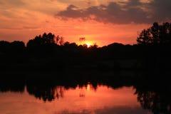Tramonto rosso di Firey sopra il lago Immagini Stock Libere da Diritti