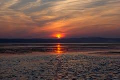 Tramonto rosso sopra l'acqua Tramonto rosso drammatico Sun che si nasconde dietro le nuvole al tramonto Immagine Stock