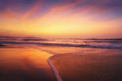 Tramonto rosso sulla riva della spiaggia Immagini Stock