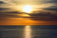 Tramonto sbalorditivo in un cielo drammatico sopra un oceano sereno fotografia stock libera da diritti