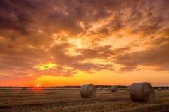 Tramonto sopra il campo dell'azienda agricola con le balle di fieno Fotografia Stock