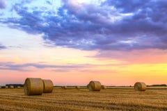 Tramonto sopra il campo dell'azienda agricola con le balle di fieno Immagine Stock