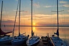 Tramonto sopra il lago nei precedenti degli yacht Immagine Stock Libera da Diritti
