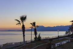 Tramonto sopra il Mar Mediterraneo Palme e montagne contro il cielo di tramonto immagini stock libere da diritti