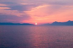 Tramonto sopra il mare con le tonalità blu e dorate nebbiose Fotografia Stock