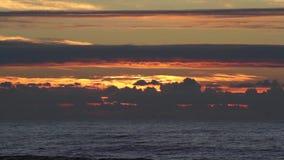 Tramonto sopra l'oceano con le piccole onde, nuvole e belle luce solare e riflessioni rosse sulla superficie dell'acqua video d archivio