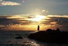 Tramonto sopra la pesca della donna del mare Fotografie Stock