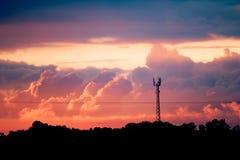 Tramonto sopra la torre del segnale del villaggio con siluette e nuvole drammatiche Immagini Stock Libere da Diritti