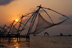 Tramonto sopra le reti da pesca cinesi a Cochin fotografia stock