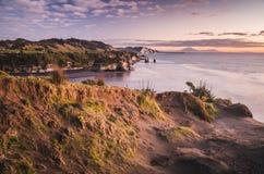 Tramonto sopra le rocce della riva di mare ed il supporto Taranaki, Nuova Zelanda Immagine Stock