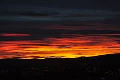 Tramonto sopra Oslo con la siluetta di Holmenkollen immagini stock libere da diritti