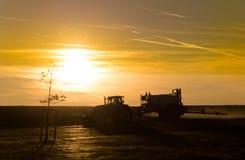 Tramonto sopra un campo con il trattore Immagini Stock Libere da Diritti