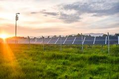 Tramonto sopra una centrale elettrica fotovoltaica con i moduli fotovoltaici per energia rinnovabile sul campo Generazione di ene immagine stock libera da diritti