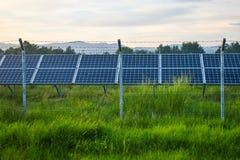 Tramonto sopra una centrale elettrica fotovoltaica con i moduli fotovoltaici per energia rinnovabile sul campo Generazione di ene fotografia stock