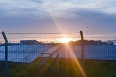 Tramonto sopra una centrale elettrica fotovoltaica con i moduli fotovoltaici per energia rinnovabile sul campo Generazione di ene fotografie stock libere da diritti