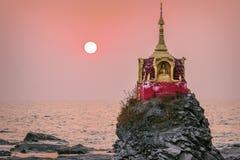 Tramonto sopra una piccola pagoda dalla spiaggia Fotografie Stock