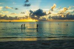 Tramonto sopra una spiaggia caraibica con i pensionanti in piedi della pagaia Immagini Stock