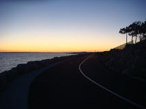 Tramonto sopra una strada dal mare Fotografia Stock Libera da Diritti