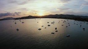 Tramonto su Ibiza, molte barche e yacht vicino alle rive, colpo aereo di navigazione archivi video