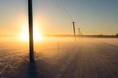 Tramonto su una strada della neve in un campo invernale Immagini Stock Libere da Diritti
