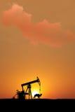 Tramonto sui giacimenti di petrolio isolati con la siluetta Fotografie Stock