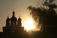Tramonto sui precedenti della chiesa dall'albero fotografia stock libera da diritti