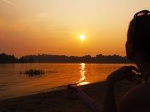 Tramonto sul fiume e sulla siluetta della giovane donna immagine stock libera da diritti