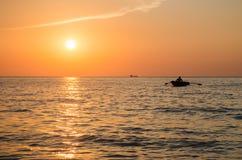 Tramonto sul mare, una barca Immagini Stock Libere da Diritti