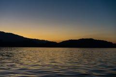 Tramonto sull'erba medica del lago con le montagne osservate dal cielo della radura della barca Fotografie Stock Libere da Diritti