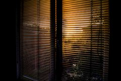 Tramonto tramite i paraocchi delle finestre immagine stock libera da diritti
