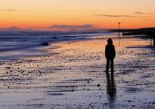 Tramonto triste della spiaggia del ragazzo Fotografie Stock