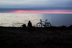Tramonto vicino al mare ed alla gente con la siluetta della bicicletta Immagini Stock Libere da Diritti