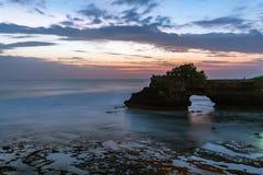 Tramonto vicino al punto di riferimento turistico famoso dell'isola di Bali - tempio del lotto & di Batu Bolong di Tanah immagine stock libera da diritti