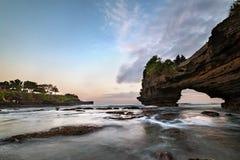 Tramonto vicino al punto di riferimento turistico famoso dell'isola di Bali - tempio del lotto & di Batu Bolong di Tanah fotografie stock