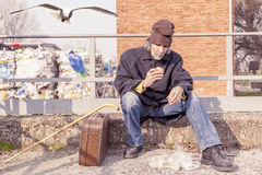 Tramp eating bread sitting in landfills. During winter time Stock Photos