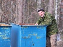 Tramp near the garbage bin Royalty Free Stock Photos
