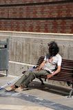 Tramp sitting on bench, Malaga. Royalty Free Stock Images