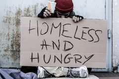 Tramp sitting on the street. With a cup for money and holding a sign with text `Homeless and hungry Stock Images