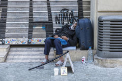 Tramp sleeping in Barcelona. Barcelona, Spain - May 26, 2015: Tramp sleeping at the gates of a closed trade in Barcelona, Spain on May 26, 2015 Royalty Free Stock Image