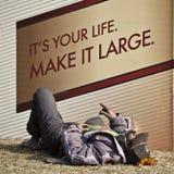 Tramp sleeping in front of a billboard  Nepal Stock Image