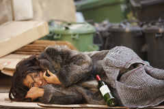 Tramp woman lying. Young tramp woman lying with bottle of wine  in bin Stock Images