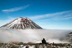 Tramperen som den har, vilar framme av den aktiva vulkan, bergfotvandraren och klättraren som har mellanmålet och, tycker om spek arkivbild