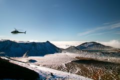 Tramping rescue helicopter in wild mountains snowy landscape with deep blue lake above the clouds, rescuing trampers, New Zealand royalty free stock photos