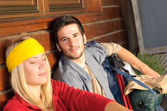 Tramping young couple backpack relax by cottage Stock Image